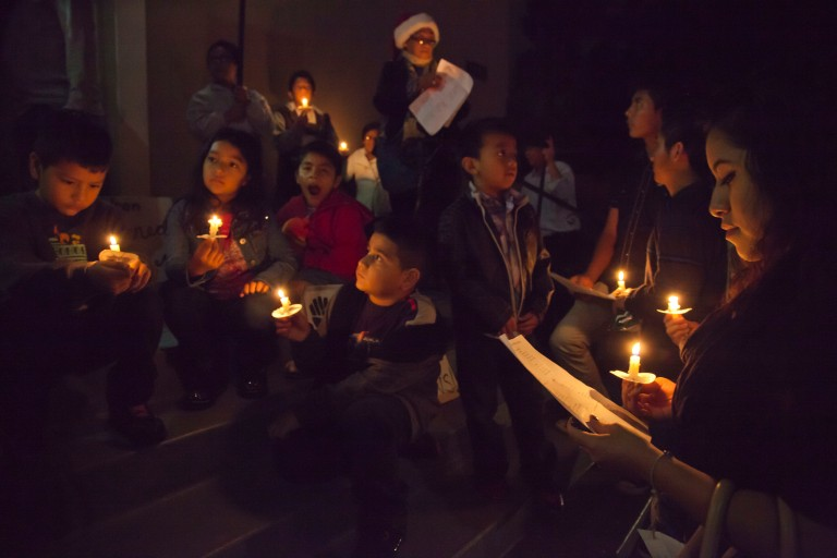 OAKLAND, CA - 18DECEMBER14 - Immigrants and immigrant rights activists celebrate the Christmas posada at a Presbyterian church in Oakland, in a candlelight vigil and teatro acting out the journey of an immigrant family seeking sanctuary from deportation. Copyright David Bacon
